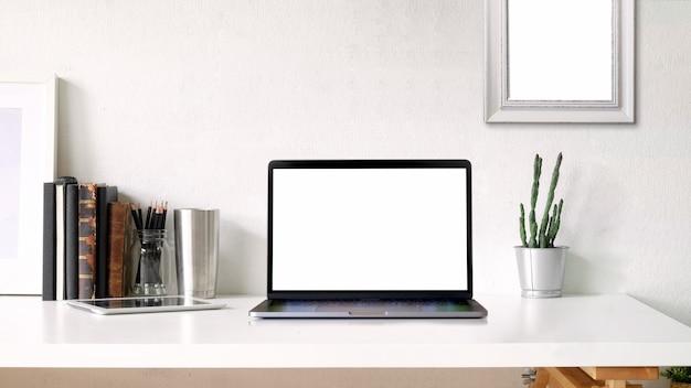 Arbeitsraum und textfreiraum. modellplakat und laptop des leeren bildschirms auf weißem schreibtisch Premium Fotos
