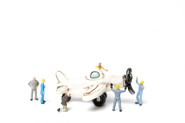 Arbeitsteam, das spielzeugflugzeug auf weißem hintergrund repariert Premium Fotos