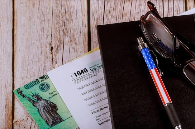 Arbeitstisch im büro des buchhalters us formular einkommenssteuer 1040 mit brille und stift und persönlichem rückerstattungsscheck Premium Fotos