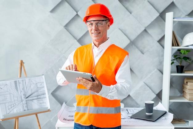 Architekt in der sicherheitsausrüstung unter verwendung der tablette Kostenlose Fotos