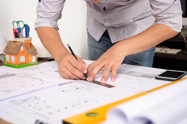 Architekt zeichnet baupläne auf planpapier mit bleistift. Premium Fotos
