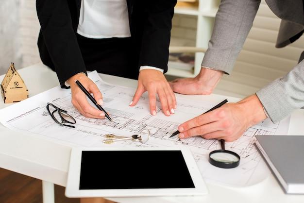 Architekten, die einen plan mit modell studieren Kostenlose Fotos