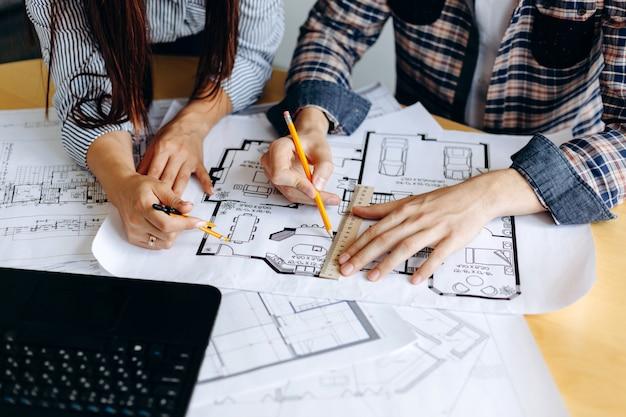 Architekten, die pläne auf einem tisch im büro betrachten Premium Fotos