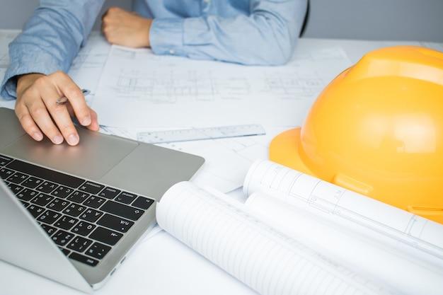 Architekten nutzen den laptop häufig für informationen zu blueprint-papier auf dem tisch. Premium Fotos