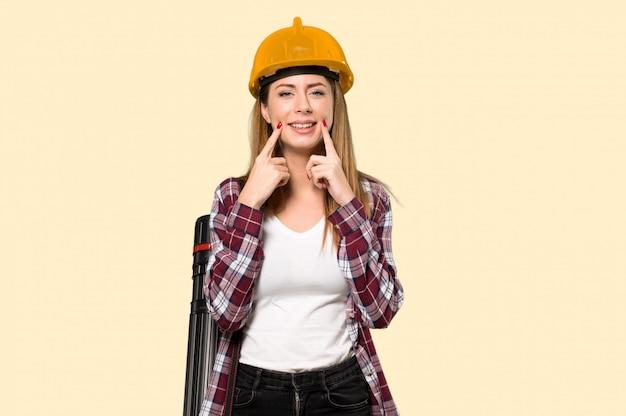 Architektenfrau, die mit einem glücklichen und angenehmen ausdruck über getrenntem gelb lächelt Premium Fotos