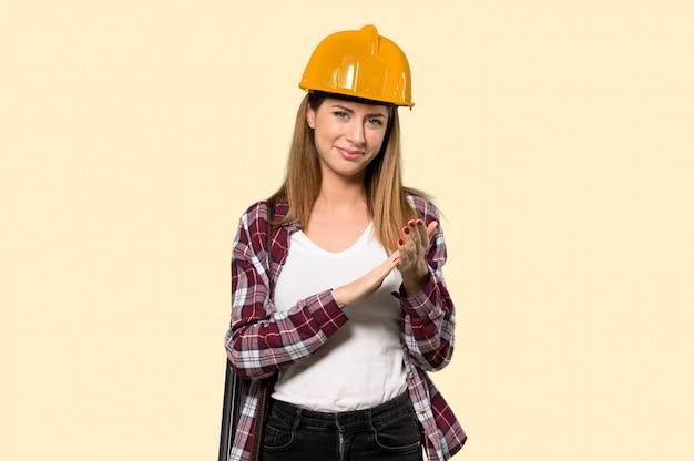 Architektenfrau, die nach darstellung in einer konferenz auf gelb applaudiert Premium Fotos