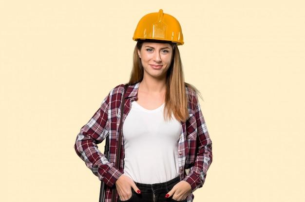 Architektenfrau, die zur frontseite über getrenntem gelb schauend lacht Premium Fotos
