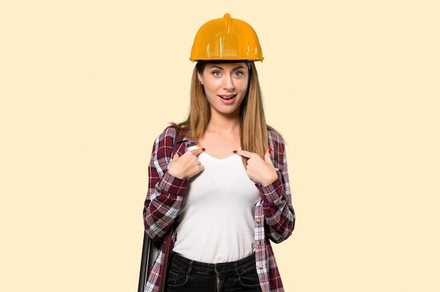 Architektenfrau mit überraschungsgesichtsausdruck über lokalisierter gelber wand Premium Fotos