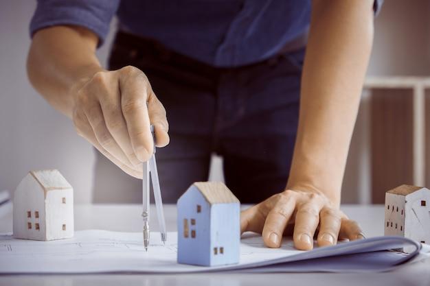 Architektenmann, der mit kompasssen und plänen für architekturplan, ingenieur skizziert ein bauprojektkonzept arbeitet. Premium Fotos