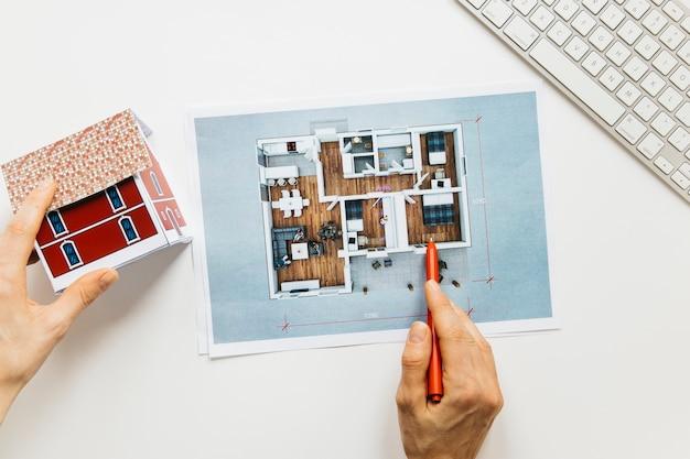 Architekturhand, die hausmodell bei der prüfung der blaupause hält Premium Fotos