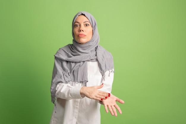 Argumentieren sie, argumentieren sie konzept.arab frau im hijab. porträt des mädchens, das am grünen studiohintergrund aufwirft. junge emotionale frau. die menschlichen emotionen, gesichtsausdruck konzept. vorderansicht. Kostenlose Fotos