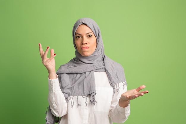 Argumentieren sie, argumentieren sie konzept.arab frau im hijab. porträt des mädchens, das im grünen studio aufwirft. Kostenlose Fotos