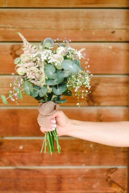 Arm der frau ihren brautblumenstrauß mit hölzernem hintergrund halten Premium Fotos