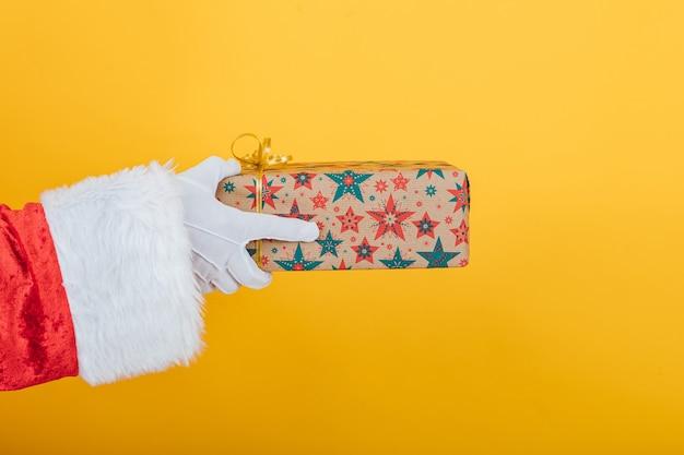 Arm des weihnachtsmannes hält ein geschenk von der linken seite auf gelb Premium Fotos