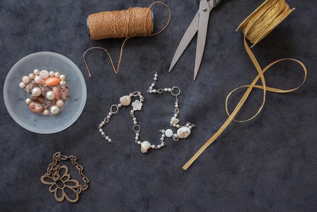 Armband mit garnrolle gemacht; perlen; schere und goldenes band auf schwarzem strukturiertem hintergrund Kostenlose Fotos