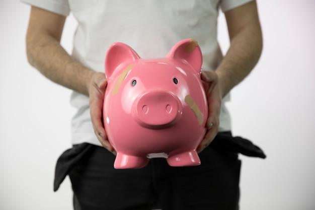 Armer mann mit leeren taschen, die große zerbrochene schweinchen mit bandagen darauf halten Premium Fotos