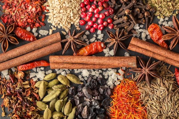 Aromatische indische gewürze auf einem grauen schiefer Premium Fotos