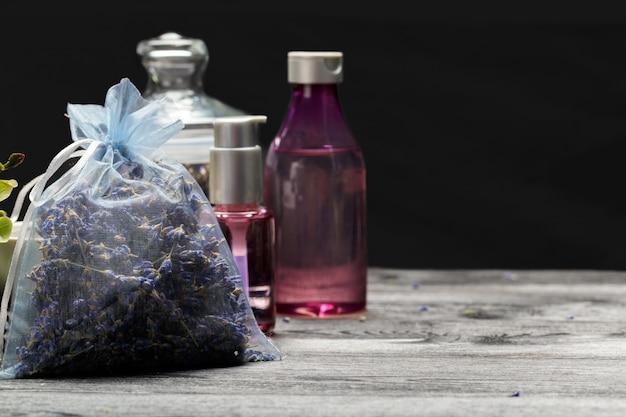 Aromatische komposition aus lavendel, kräutern, kosmetik und salz auf dunkler tischplatte Premium Fotos