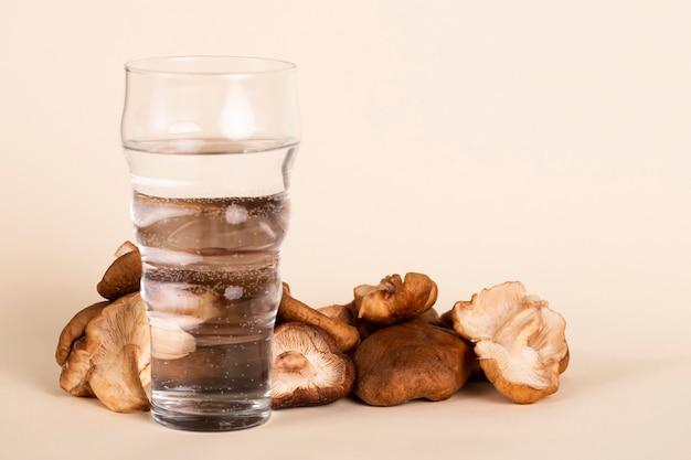 Arrangement mit einem glas wasser und champignons Kostenlose Fotos