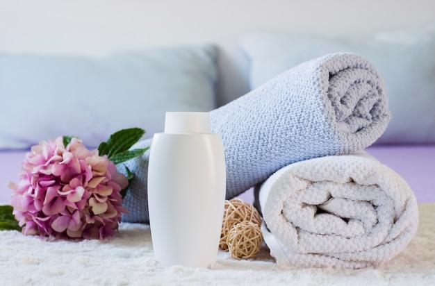 Arrangement mit handtüchern, flasche und blume auf dem bett Kostenlose Fotos