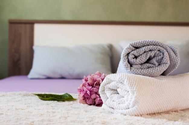 Arrangement mit handtüchern und blumen auf dem bett Kostenlose Fotos