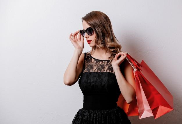 Artfrau in der sonnenbrille mit einkaufstaschen auf weißer wand Premium Fotos