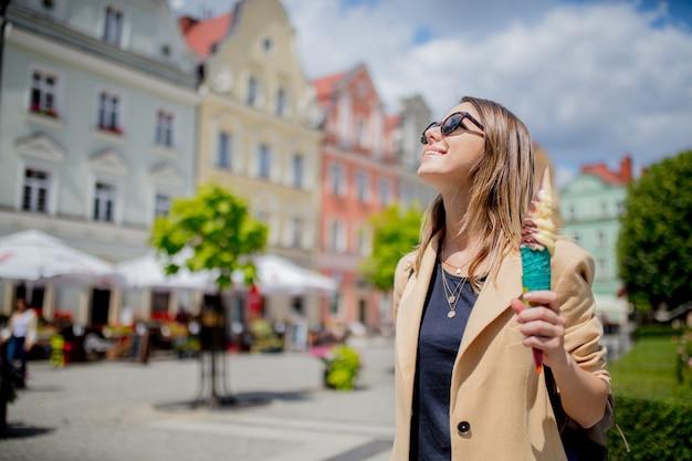Artfrau in der sonnenbrille und in der eiscreme in gealtertem stadtzentrumquadrat. Premium Fotos