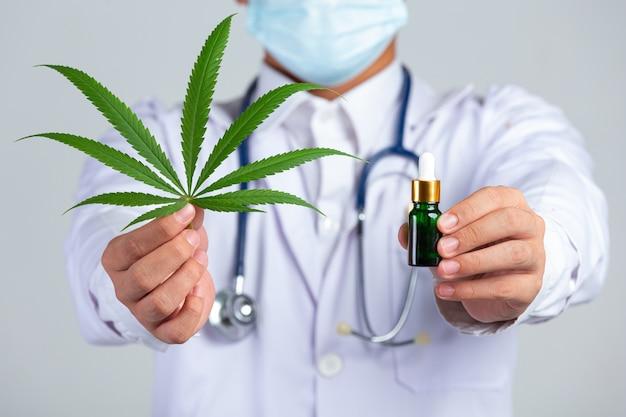 Arzt, der cannabisblatt und flasche cannabisöl auf weißer wand hält. Kostenlose Fotos