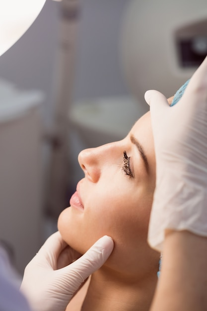 Arzt, der das gesicht der frau auf kosmetische behandlung untersucht Kostenlose Fotos