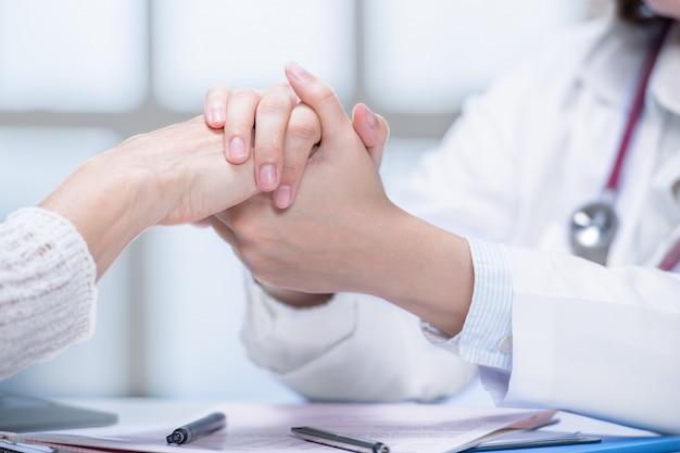 Arzt, der patienten durch händchenhalten in der krankenhauseinstellung beruhigt Premium Fotos