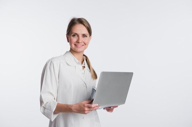 Arzt frau lächeln halten tablet pc, mit computer. krankenschwester über weißem hintergrund isoliert Premium Fotos