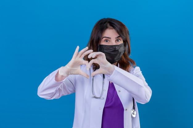 Arzt mittleren alters, der weißen kittel in schwarzer schützender gesichtsmaske und mit stethoskop trägt, das romantische herzgeste über brust macht Kostenlose Fotos
