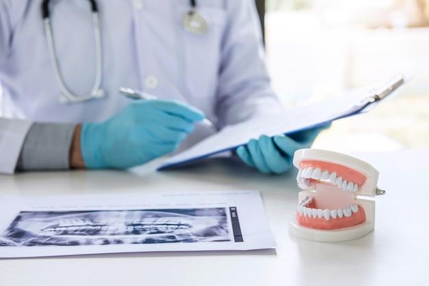 Arzt oder zahnarzt, der mit röntgenfilmen, modellen und ausrüstungen für die behandlung und analyse von zahnkrankheiten arbeitet Premium Fotos
