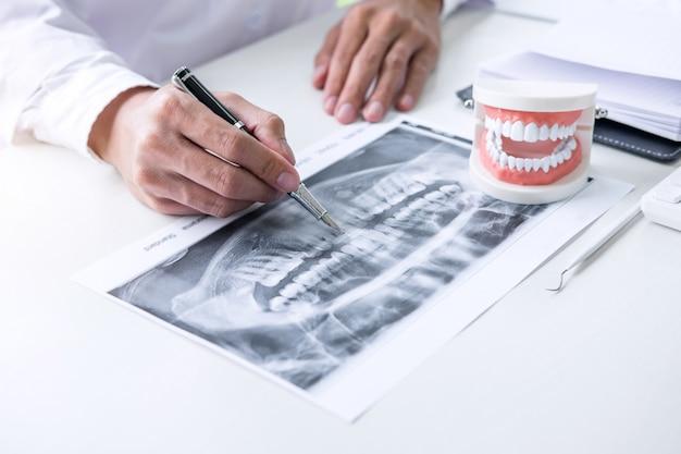 Arzt oder zahnarzt schreiben einen bericht, der mit einem zahnröntgenfilm arbeitet Premium Fotos