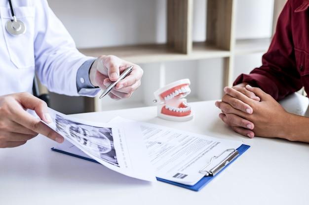 Arzt oder zahnarzt schreiben einen bericht, der mit einem zahnröntgenfilmmodell arbeitet Premium Fotos