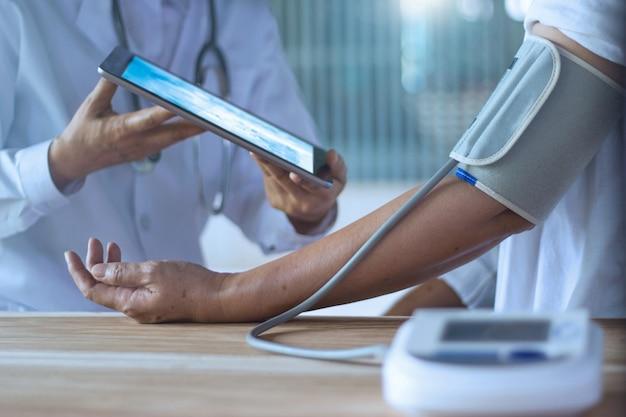 Arzt prüft den blutdruck Premium Fotos