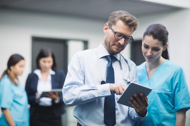 Arzt und krankenschwester diskutieren über digitales tablet Kostenlose Fotos