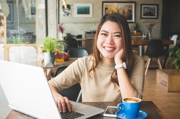 Asain frau, die in der kaffeestube glücklich mit lächeln arbeitet Premium Fotos