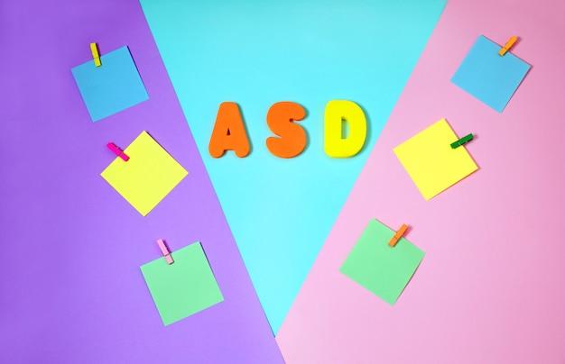 Asd, autismus-konzept mit farbpapieraufklebern auf mehrfarbenhintergrund Premium Fotos