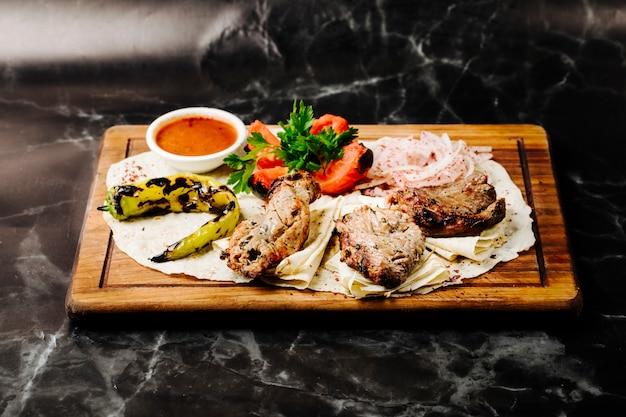 Aserbaidschanischer rindfleisch-barbecue-kebab serviert auf lavash mit gegrilltem pfeffer, tomaten und bbq-sauce. Kostenlose Fotos