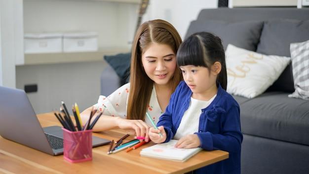 Asian happy mutter und tochter nutzen laptop, um zu hause online über das internet zu lernen. e-learning-konzept während der quarantänezeit. Premium Fotos