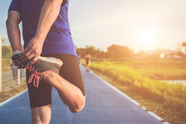 Asian läufer wärmen seinen körper vor dem start auf der straße Premium Fotos