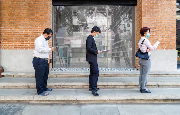 Asiaten tragen eine maske und halten soziale distanz, um die verbreitung von covid-19 zu vermeiden Premium Fotos