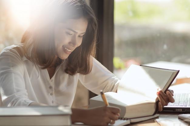 Asiatin arbeits- und lesebuch mit glücklichem. Premium Fotos