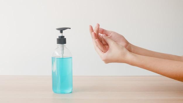 Asiatin, die alkohol-gel-händedesinfektionsmittel verwendet, waschen hand zum schutz des coronavirus. frau drückt alkoholflasche, um die hand für hygiene zu reinigen, wenn soziale distanzierung zu hause bleibt und selbstquarantänezeit. Kostenlose Fotos