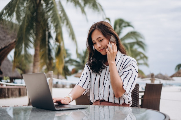 Asiatin, die an laptop auf ferien arbeitet Kostenlose Fotos