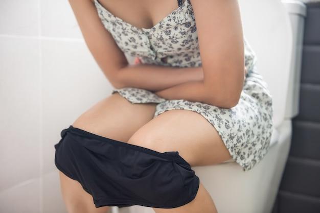 Asiatin, die auf toilette im badezimmer sitzt und ihren schmerzlichen magen des schlechten stomas hält Premium Fotos