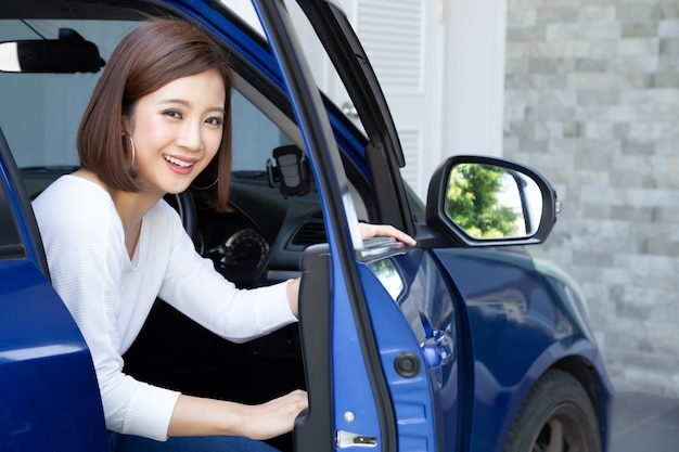 Asiatin, die aus einem auto steigt Premium Fotos