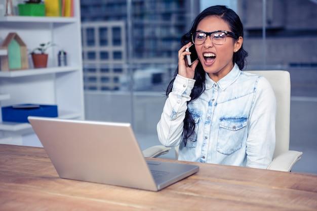 Asiatin, die beim telefonanruf im büro schreit Premium Fotos