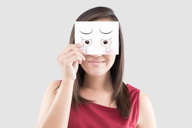 Asiatin, die ein weißbuch mit einem karikaturschreigesicht auf ihr vor ihren augen hält Premium Fotos